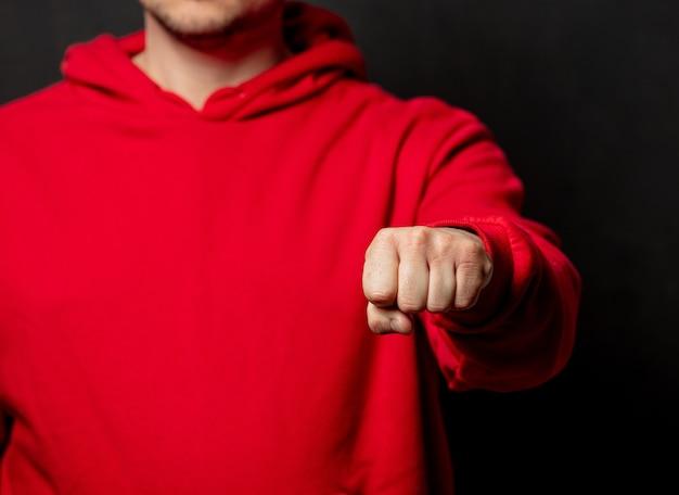 Парень в красной толстовке показывает жест кулаком на темной стене