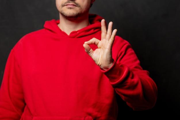 Парень в красной толстовке показывает жест ок на темной стене