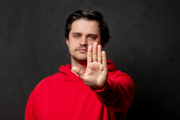 Парень в красной толстовке показывает жест стоп на темной стене