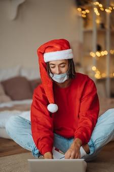 Парень в новогодней шапке возле ноутбука общается через видеозвонки