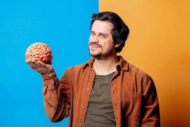 Парень в рубашке держит человеческий мозг на желтом и синем фоне