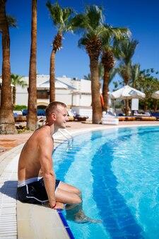 밝은 태양 아래 수영장에서 반바지를 입은 남자 목욕