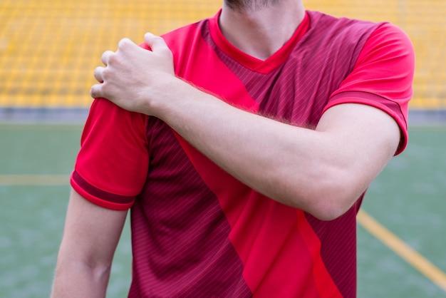 Парень в спортивной одежде трогает плечо