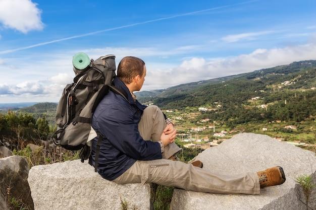 バックパックで休んでいるキャンペーンの男。素晴らしい景色を望む山々。