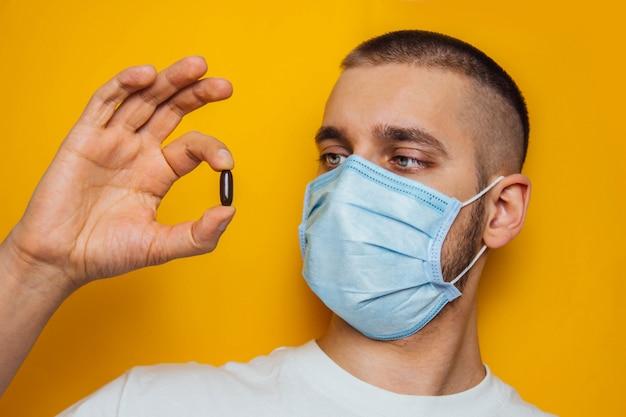 마스크에있는 사람은 코로나 바이러스의 약을 손에 든다. 면역 체계를 강화시키는 비타민. 집에 앉아 감기, 독감, 바이러스, 검역, 전염병 개념. 어려운 선택.
