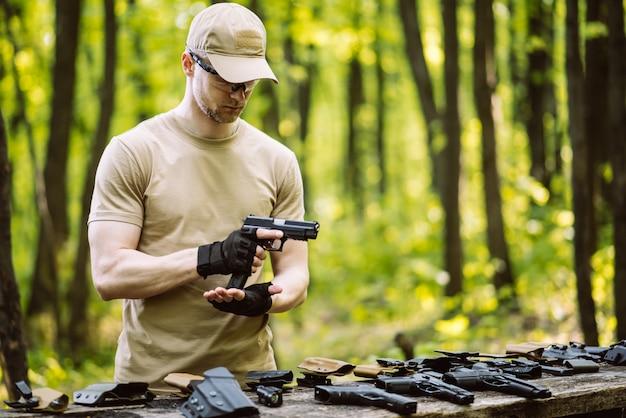 Парень в лесу проверяет свое оружие для спортивной стрельбы