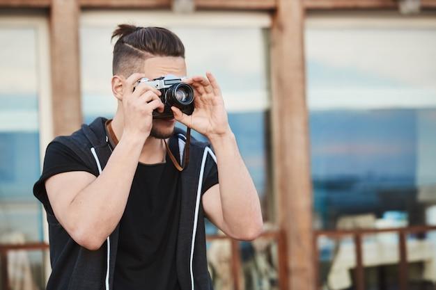 通りで写真を撮って、カメラを通して見る流行の服の男