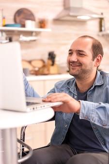 キッチンでラップトップを使用してビデオ会議で笑っている車椅子の男。事故後に統合した歩行障害のある障害者麻痺障害者。