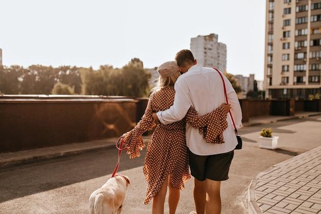 흰 셔츠와 반바지를 입은 남자가 폴카 도트 복장으로 여자 친구를 껴안고 있습니다. 그들의 흰색 래브라도 산책하는 커플.