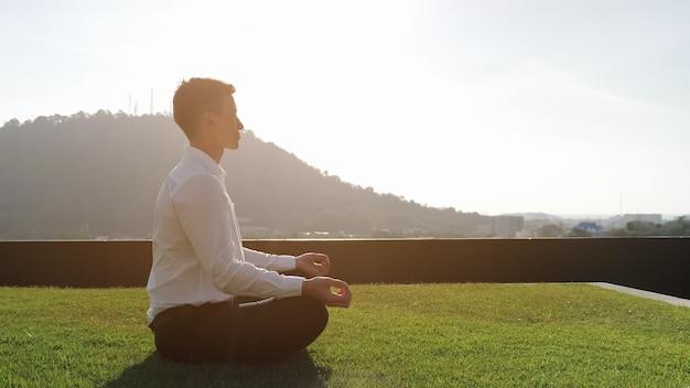 Парень в белой рубашке медитирует, сидя в позе лотоса на траве террасы отеля при солнечном свете на фоне зеленого холма и синего неба, вид сбоку, копия пространства