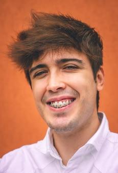 オレンジ色の壁に笑みを浮かべて白いシャツの男