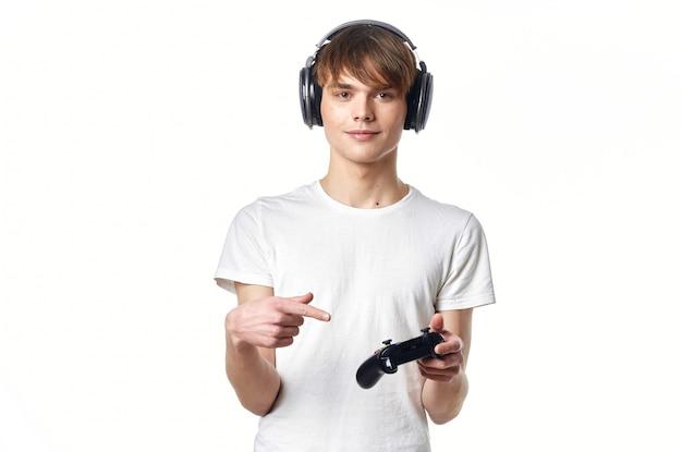 ビデオゲームのゲーマーを再生するヘッドフォンと白いtシャツの男。高品質の写真