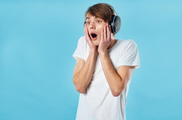 ヘッドフォン感情音楽技術青い背景を身に着けている白いtシャツの男