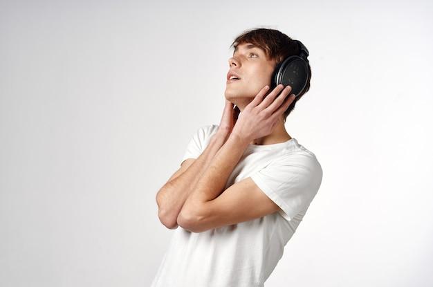 ヘッドフォン音楽技術の明るい背景を持つ白いtシャツの男