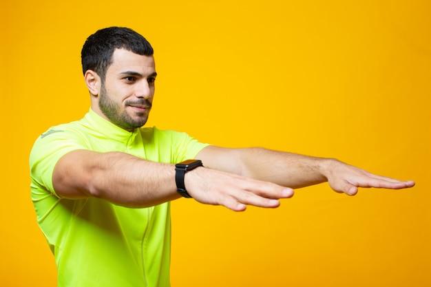 Парень в желтой футболке вытянул руки вперед