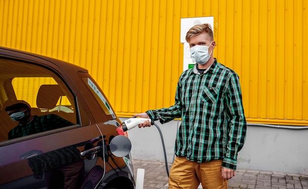 男は充電ノズルを持って電気自動車を充電し、環境にやさしい車が屋外でエネルギーを供給するプロセスを楽しんでいます。