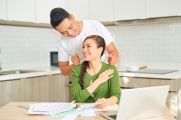 彼女がラップトップで働いている間、男は彼のガールフレンドをマッサージしています