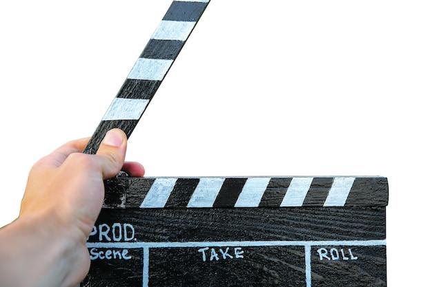남자는 흰색 배경에 고립 된 검은 clapperboard를 들고 있습니다. 남자는 아마추어 영화 영화를 감독하고 촬영하고 있습니다.