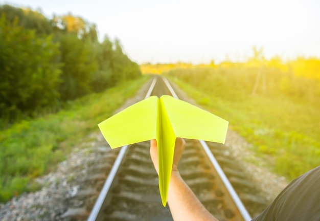Парень держит желтый бумажный самолетик ручной работы. фото концепции свободы с рельсовыми путями. мотивация образа жизни путешествий. отрасль железнодорожного транспорта.