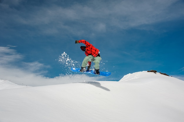 Guy is jumping on a blue snowboard from a snowy mountain