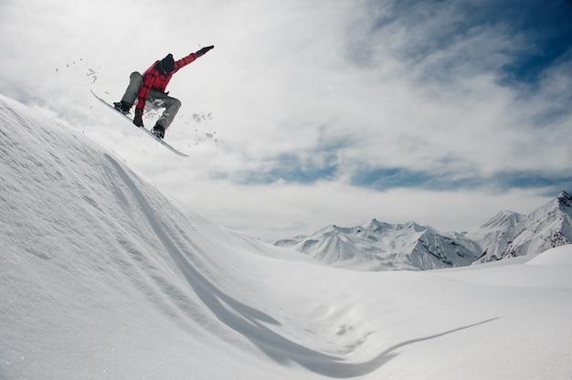남자는 푸른 하늘과 눈 덮인 산봉우리에 대 한 스노우 보드에 점프