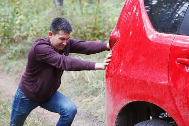 Парень толкает красную машину.