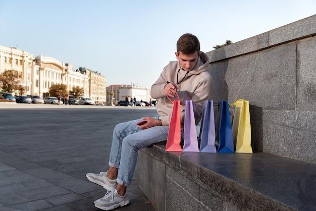 남자는 성공적인 쇼핑 후 휴식을 취하고 쇼핑백 구매를 고려하고 있습니다.