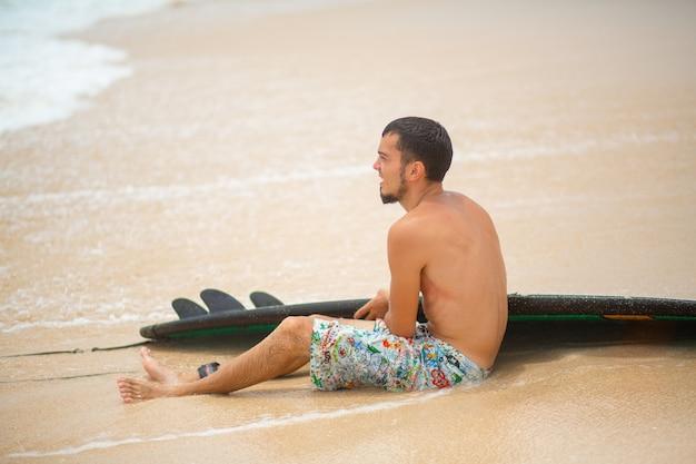 男はサーフィンに乗った後、砂浜の熱帯のビーチで休んでいます。夏休みの健康的なアクティブなライフスタイル