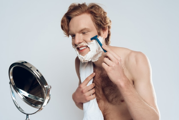 Guy is shaving with razor, looking in mirror. male beauty.