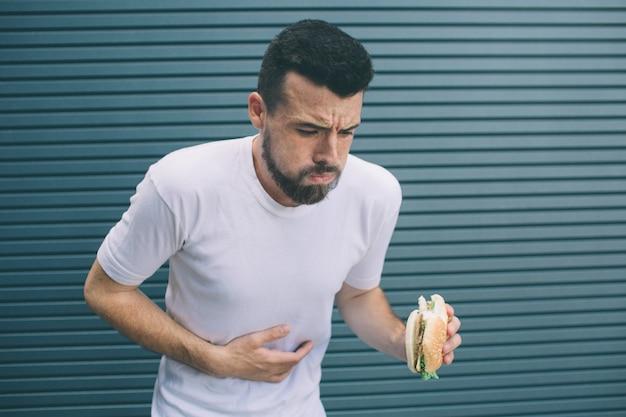Парень болен он держит гамбургер в руке и смотрит вниз. человек собирается рвать. изолированные на полосатый
