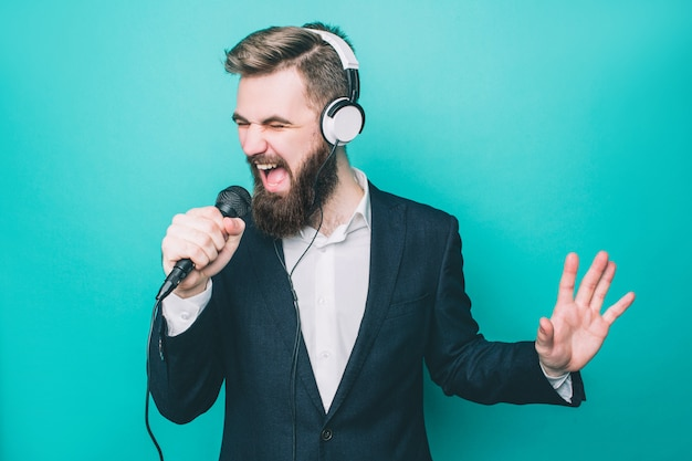 Guy is singing with microphone and wearing headphones