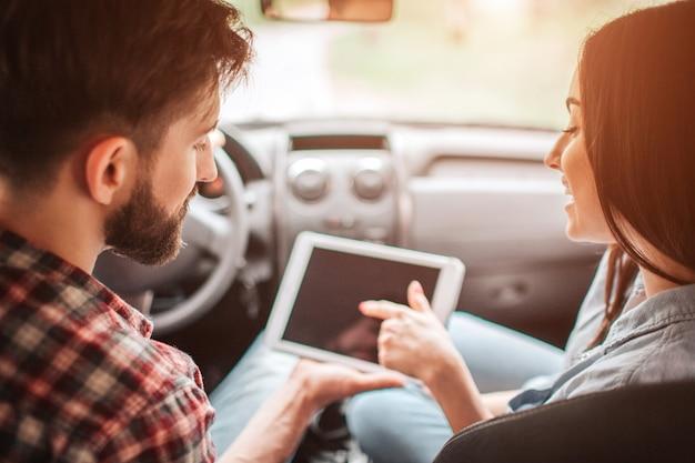 男は女の子と車に座って、暗い画面でタブレットを見ています。