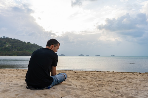 A guy is sitting on a sandy beach looking at the water. enjoys the beautiful scenery of nature.