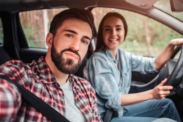 Парень делает селфи в машине со своей девушкой. она смотрит на камеру и улыбается. девушка держит руки на руле.