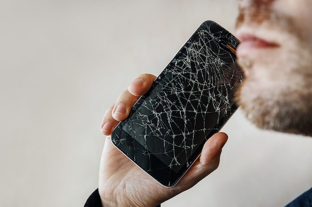 The guy is talking on the phone with a broken screen. black smartphone with cracked glass in a man's hand. copy space. copyspace.