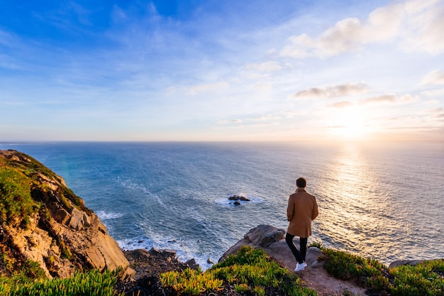 The guy is walking on a hilly stony coast with a magnificent views