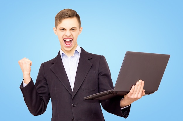 Guy in a jacket and blue shirt with a laptop rejoices, isolated on a blue background