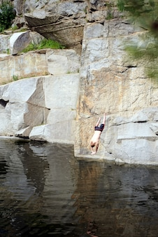 The guy jumps from the rock in water in a canyon. fearless person. big height and deep lake.
