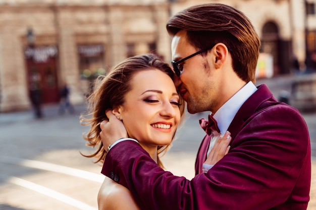 The guy kisses a beautiful girl in the beautiful sunny morning