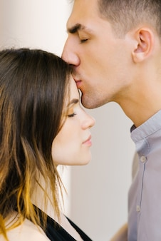 The guy kisses the girl on the forehead. valentine's day