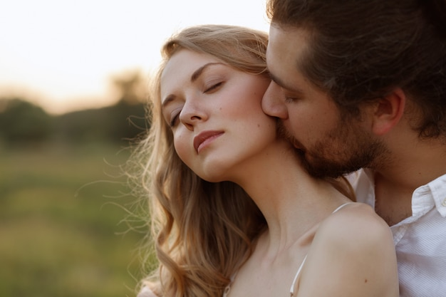 The guy kisses the girl in the neck. close-up portrait