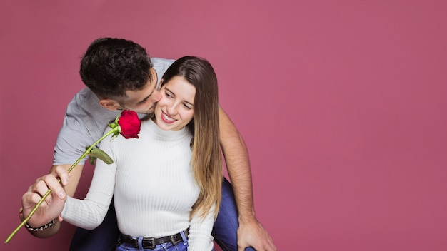 Guy kissing and presenting fresh rose to attractive cheerful lady