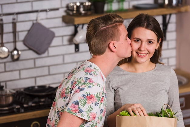 Guy kissing smiling girlfriend in kitchen
