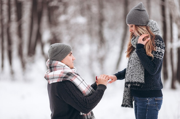 A guy kneeling down puts a wedding ring on a girl's hand, making a proposal to marry in a snowy forest in winter