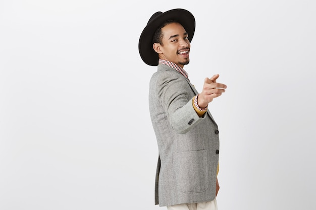 Guy knows how to find key to women hearts. flirty confident dark-skinned heartbreaker in stylish clothes and black hat, pointing with index finger, smiling with self-assured face
