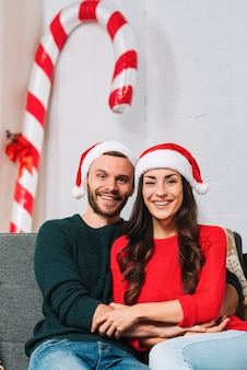 Guy and lady in party hats sitting on sofa