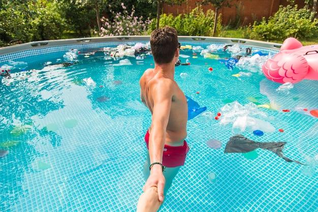 男は、ゴミの入ったプールに案内します。