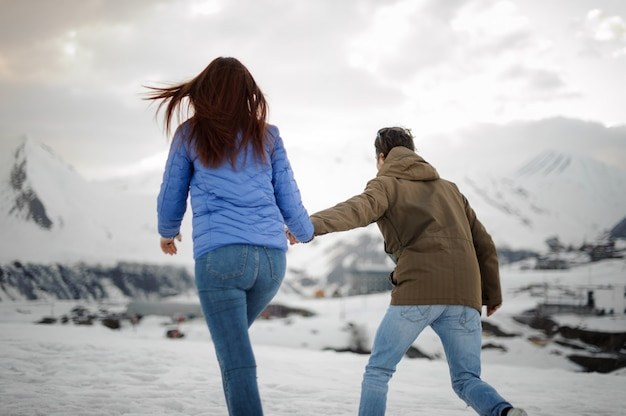 Guy leads a girl for a walk towards the snow mountains