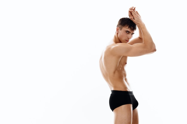 Guy on a light background with arms raised up naked torso bodybuilder. high quality photo
