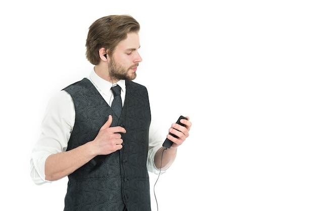 男は音楽を聴きます。白い背景で隔離のmp3プレーヤーを持つ男。オーディオブックと新技術。音楽とリラックス。携帯電話、コピースペースとヘッドセットのビジネスマン